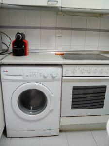 Fogão e maquina de lavar roupa convivendo lado a lado na cozinha.